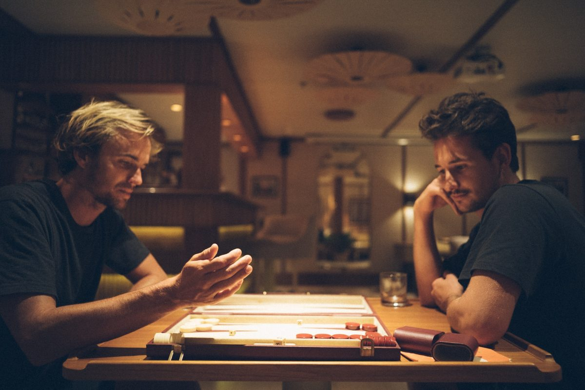 Surfers playing backgammon during secret surf mission on Kudanil Explorer